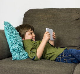 38984101 - boy laying relaxed on sofa playing on his tablet